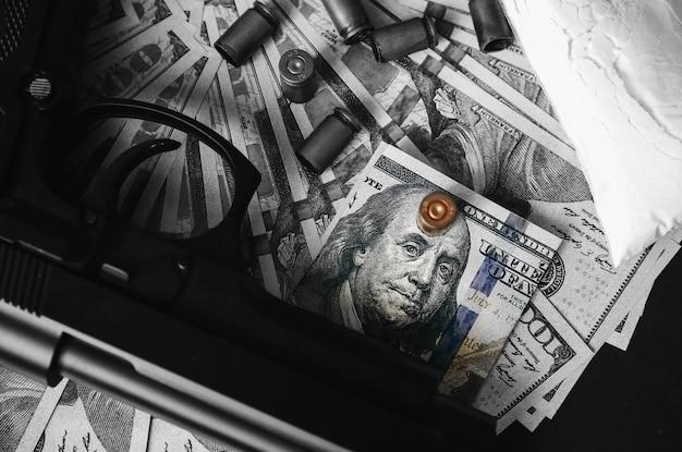 Pistolet z kulami leżącymi na stole. problemy kryminalne. leki i pieniądze na czarnym tle. nielegalna sprzedaż. dolary.