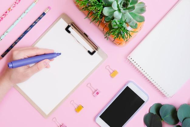 Pisząca ręka z kancelarią płaską na różowo
