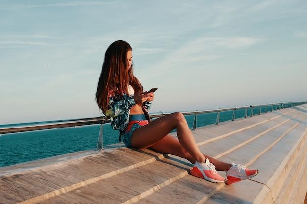 Pisze do swojej przyjaciółki. atrakcyjna młoda kobieta za pomocą smartfona siedząc w pobliżu plaży na świeżym powietrzu