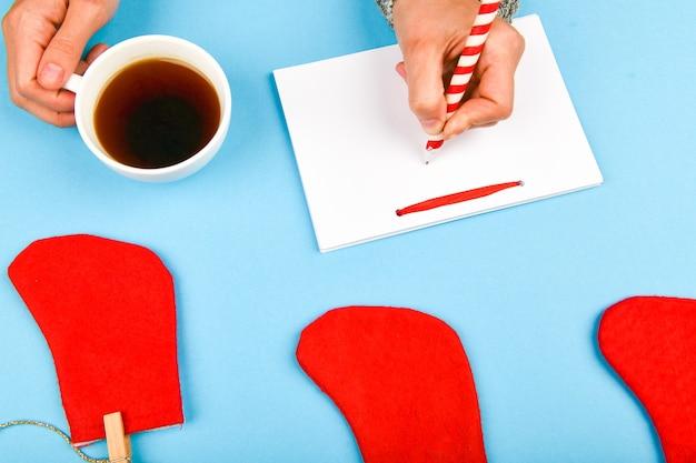 Pisze życzenia kubkiem kawy. marzenia o planach celów tworzą listę do napisania noworocznej koncepcji świątecznej w zeszycie