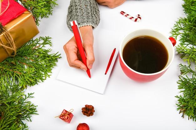 Pisze życzenia kubkiem kawy
