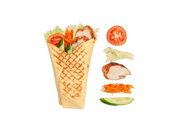 Pita gyros i składniki. zawiera: sałatę, filet z kurczaka, marynowaną marchewkę, ogórek i pomidory. białe tło. odosobniony.