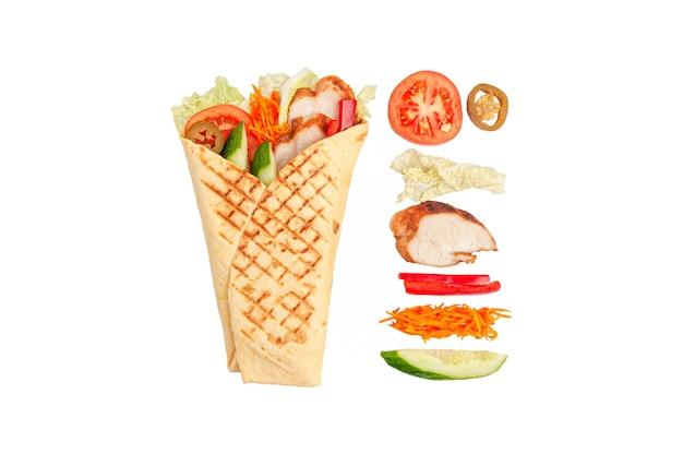 Pita gyros i składniki. zawiera: sałatę, filet z kurczaka, marynowaną marchewkę, papryczki jalopeno, paprykę, ogórek i pomidory. białe tło. odosobniony.
