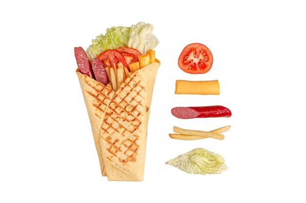 Pita gyros i składniki. zawiera: sałatę, wędzone kiełbaski, frytki, ser cheddar i pomidory. białe tło. odosobniony.