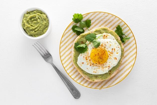 Pita płaska z pastą z awokado i jajkiem sadzonym na talerzu widelcem