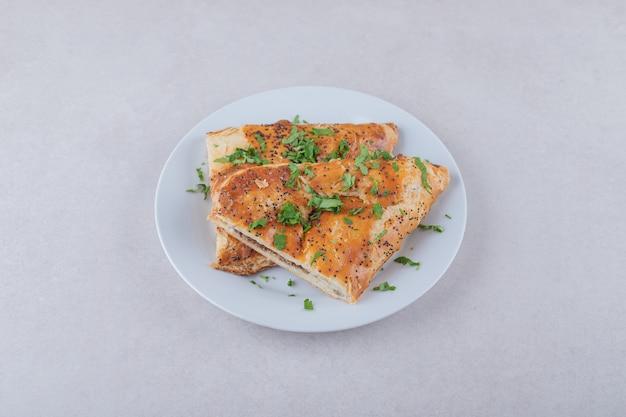 Pita sezamowa z posiekaną natką pietruszki na talerzu, na marmurze.