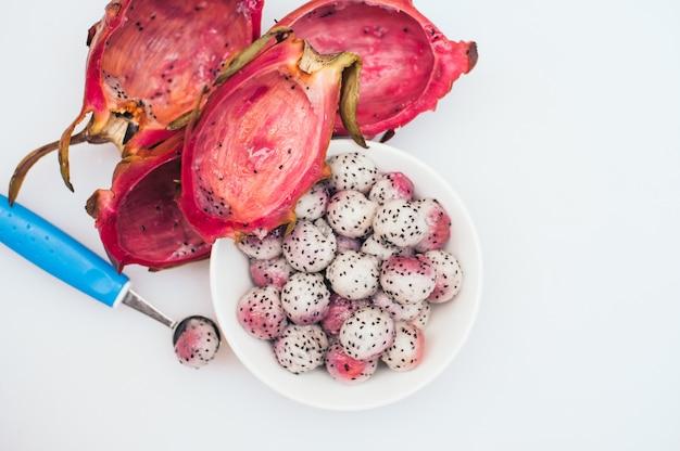 Pitahaya wykonujący ręcznie w piłkach na białym tle. pokrojone owoce tropikalne. podawanie deserów. rzeźbione owoce. smocze kulki owocowe. żywe kolory. koncepcja zdrowego żywienia
