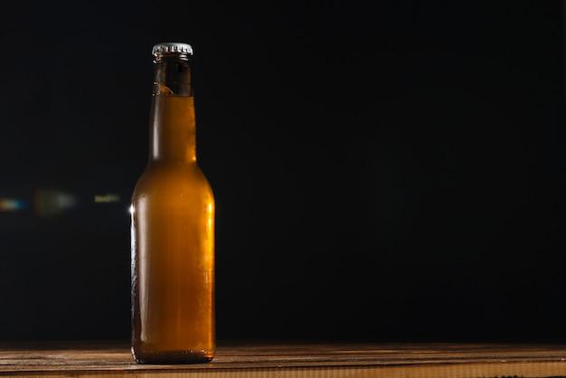 Piwna butelka na drewnianym biurku