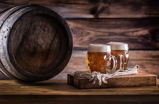 Piwo. dwa zimne piwa. piwo beczkowe. piwo z beczki. złote piwo. złote piwo. dwa złote piwa z pianką na wierzchu. lane zimne piwo w szklanych słoikach w domowym pubie hotelowym lub restauracji. martwa natura.