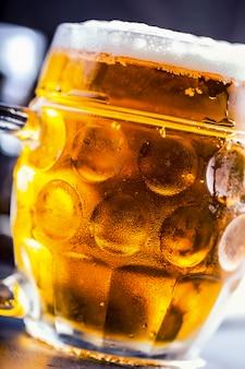 Piwo. dwa zimne piwa. piwo beczkowe. piwo z beczki. złote piwo. złote piwo. dwa złote piwa z pianką na wierzchu. lane zimne piwo w szklanych słoikach w pubie hotelowym lub restauracji. martwa natura.