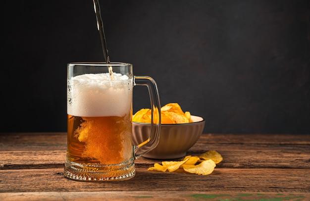 Piwo i frytki na brązowym tle. nalewanie piwa do szklanki. widok z boku, miejsce na kopiowanie.