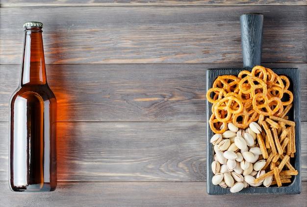 Piwo i przekąski na brązowym drewnianym