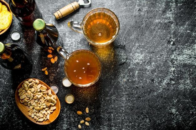Piwo i przekąski w miseczkach. na tle rustykalnym