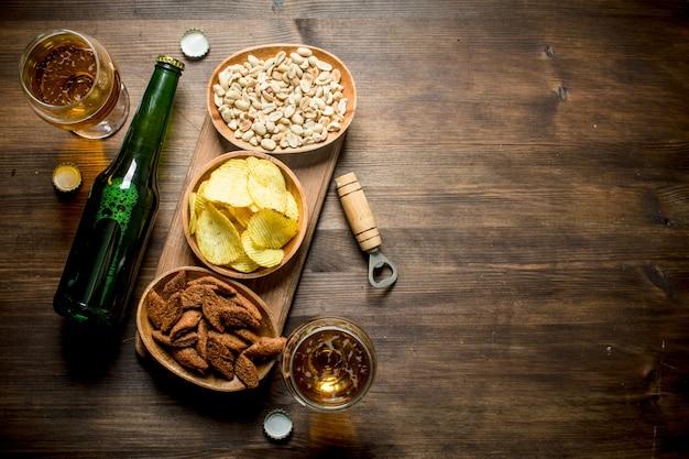Piwo i różne przekąski w miseczkach. na drewnianym tle