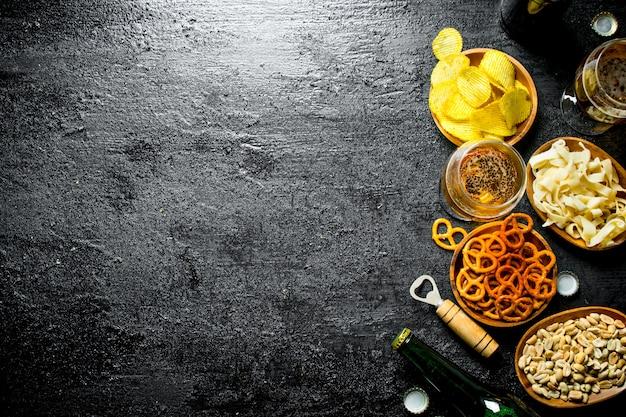 Piwo i różnego rodzaju przekąski w miseczkach. na czarnej powierzchni rustykalnej