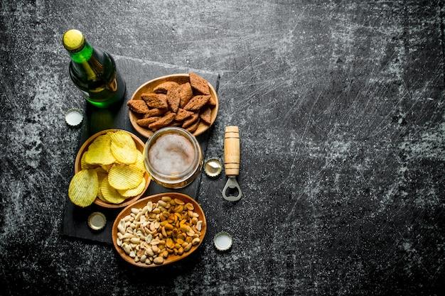 Piwo i różnego rodzaju przekąski w miseczkach. na czarnym tle rustykalnym