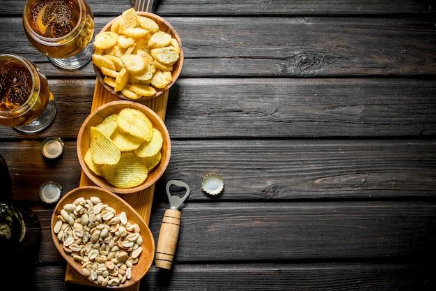 Piwo i różnego rodzaju przekąski w miseczkach na desce do krojenia. na czarnej drewnianej powierzchni