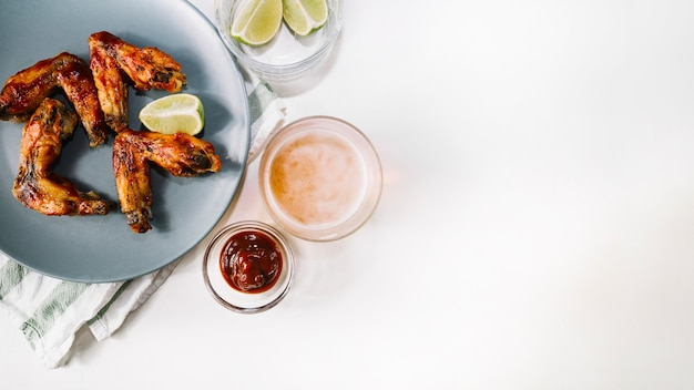 Piwo i sos w pobliżu skrzydeł z grilla
