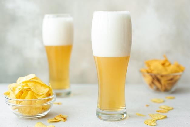 Piwo jasne z pikantnymi chipsami ziemniaczanymi w wysokich szklankach na białym stole