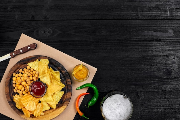 Piwo lagerowe i przekąski na czarnym drewnianym stole orzechy widok z góry z copyspace