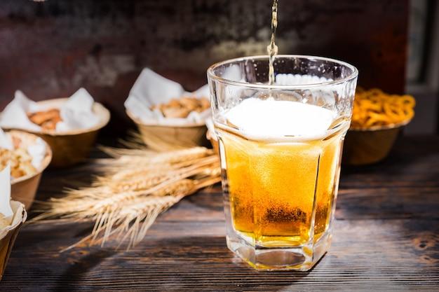 Piwo leje się do szklanki przy talerzach z pistacjami, małymi preclami i orzeszkami ziemnymi na ciemnym drewnianym biurku. koncepcja żywności i napojów