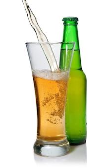 Piwo leje się z do szkła na białym tle z butelką na białym tle