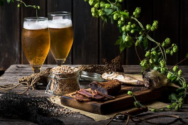 Piwo martwa natura z rybami i butelkami. basturma mięsna. oktoberfest. sucha ryba i suszone mięso. wiejski posiłek