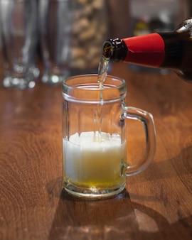 Piwo o dużym kącie rozlewa się z butelki na kufel