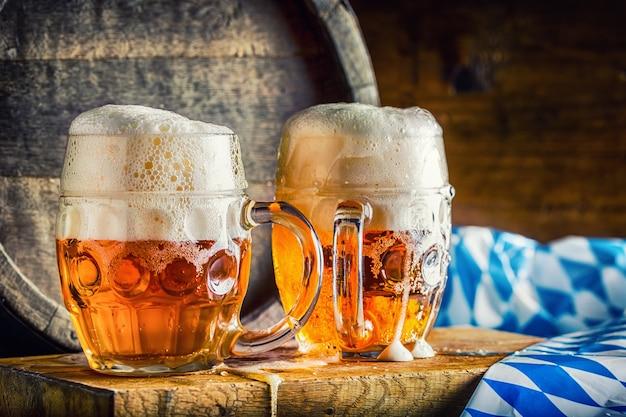 Piwo. oktoberfest.dwa zimne piwa. piwo beczkowe. piwo z beczki. złote piwo. złote piwo. dwa złote piwa z pianką na wierzchu. lane zimne piwo w szklanych słoikach w pubie hotelowym lub restauracji. martwa natura.