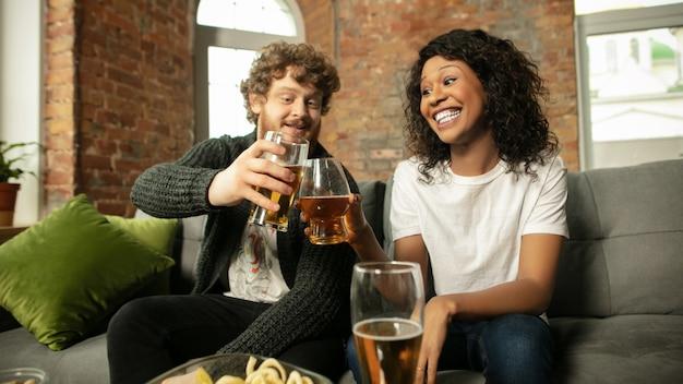 Piwo. podekscytowana para, przyjaciele oglądający mecz sportowy, mistrzostwa w domu. wieloetniczni przyjaciele, kibice kibicujący ulubionej drużynie sportowej