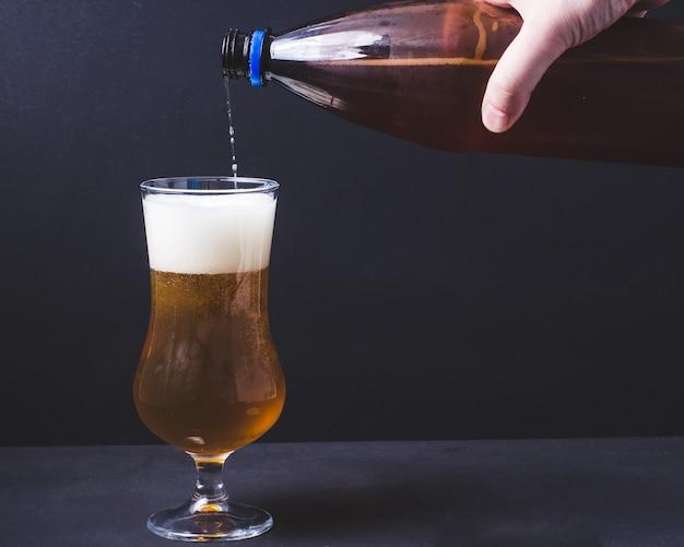 Piwo rzemieślnicze wlewa się do szklanki z plastikowej butelki. ale lub lager ze słodu pilzneńskiego.