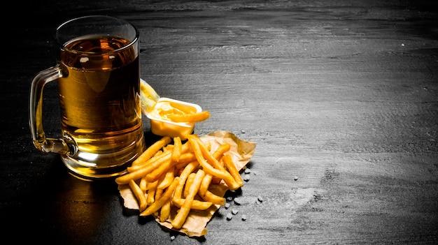 Piwo. świeże piwo i frytki z sosem musztardowym na tablicy.