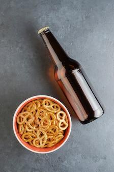 Piwo w butelce z ciemnego szkła i słony precel