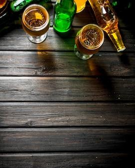 Piwo w butelkach i szklankach na rustykalnym stole