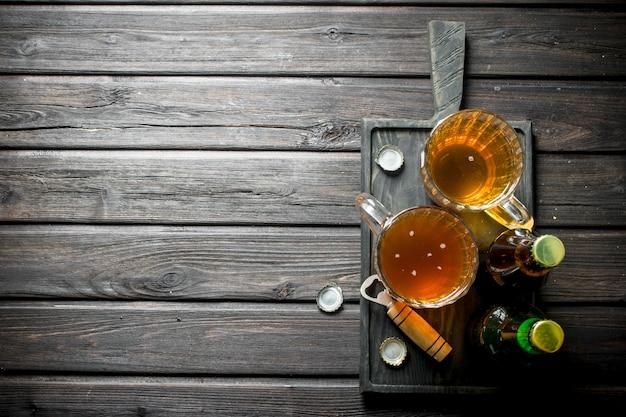 Piwo w kuflach i butelkach z otwieraczem na desce do krojenia. na czarnym tle drewnianych
