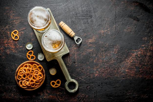 Piwo w okularach na stojaku i przekąski w misce. na ciemnym tle rustykalnym