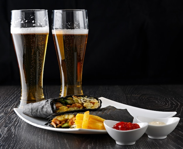 Piwo w szklance i shawarma w chlebie pita kroi się i kładzie na drewnianej powierzchni