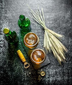 Piwo w szklankach i butelkach z bukietem kłosków na rustykalnym stole