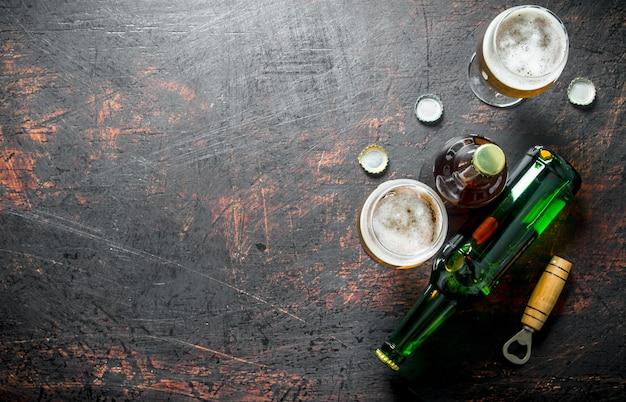 Piwo w szklankach i butelkach z otwieraczem i pokrywkami. na tle rustykalnym