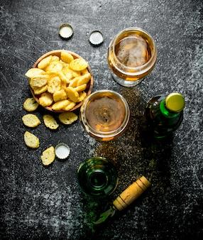 Piwo w szklankach i okruchy w misce. na rustykalnym stole