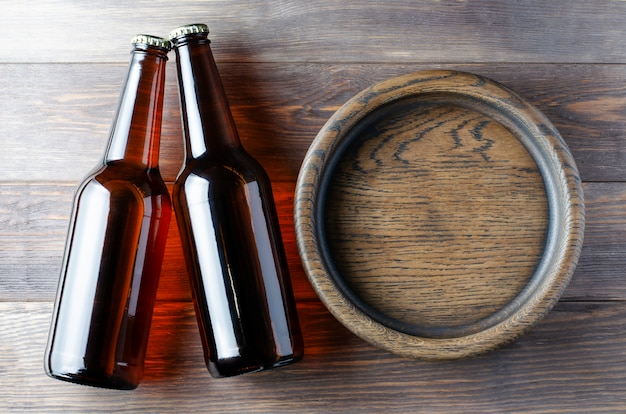 Piwo w szklanych butelkach i drewniany talerz na przekąski. brązowe drewniane tła.