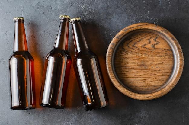 Piwo w szklanych butelkach i drewnianym talerzu