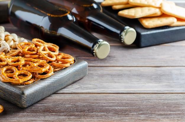 Piwo w szklanych butelkach i słone przekąski do piwa w drewnianych naczyniach. styl rustykalny. brązowe drewniane tła. skopiuj miejsce.