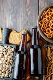 Piwo w szklanych butelkach i słone przekąski do piwa w drewnianych naczyniach. styl rustykalny. brązowe drewniane tła.