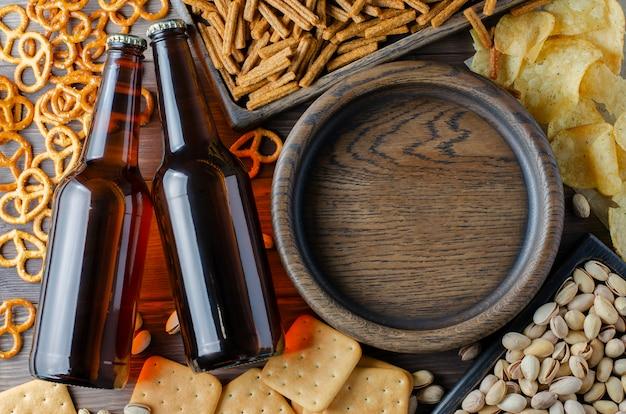 Piwo w szklanych butelkach i słone przekąski do piwa w drewnianych naczyniach