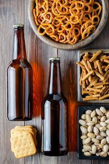 Piwo w szklanych butelkach i słone przekąski do piwa w drewnianych naczyniach.