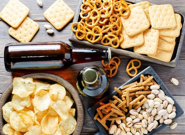 Piwo w szklanych butelkach i słone przekąski do piwa.