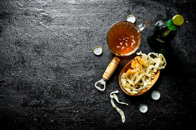 Piwo w szklanym kubku i przekąski w misce. na czarnym tle rustykalnym
