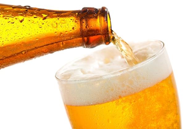 Piwo wlewając do szkła na białym tle