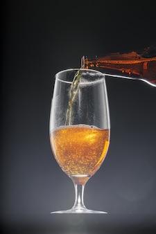 Piwo wlewając do szklanki na czarnym tle